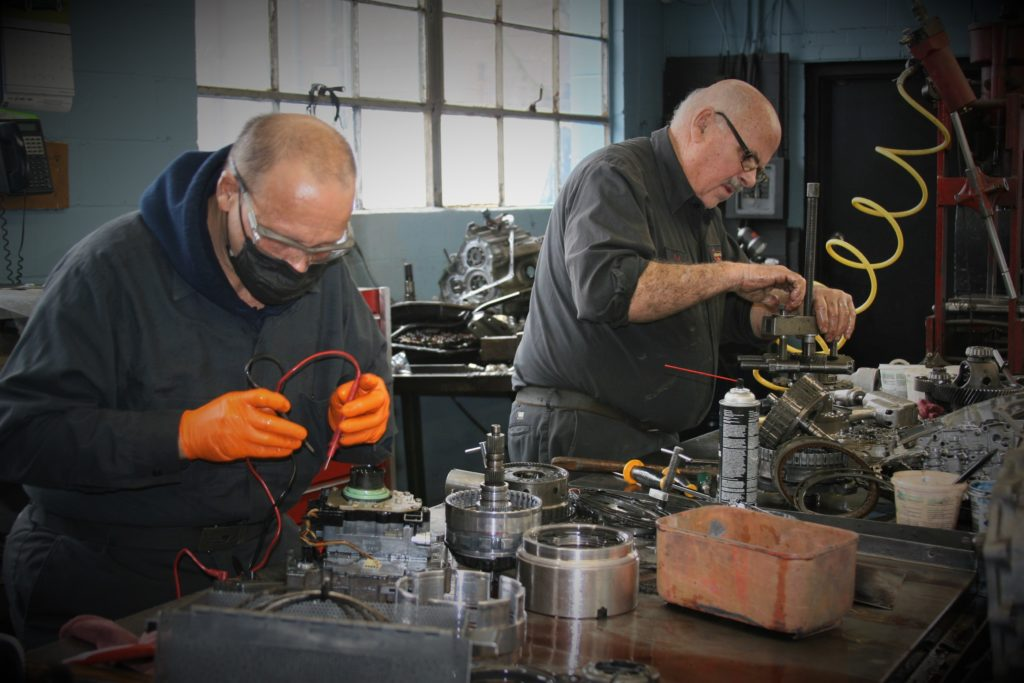 Two employees working on repairing car parts