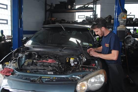 Tech working on a vehicles computer diagnostics